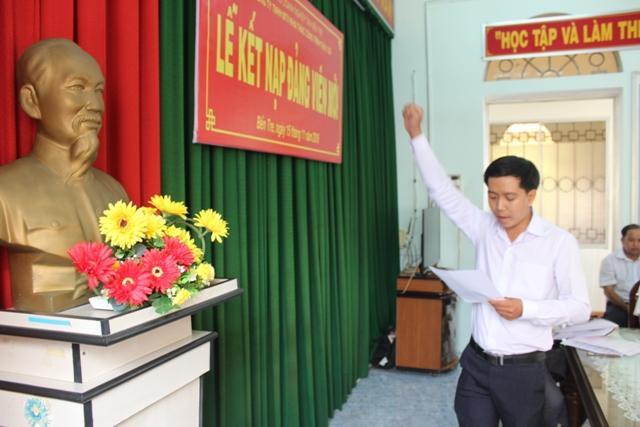 Đồng chí Trần Trọng Ân tuyên thệ dưới cờ Tổ quốc, cờ Đảng và chân dung Chủ tịch Hồ Chí Minh